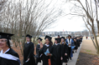 Excited graduates walk the academic processional from Webb Center to the Ted