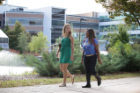 Two young female students walking on-campus.