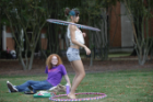 Young female student hula hooping on Kaufman Mall